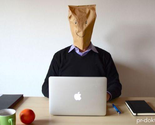 Mann am Schreibtisch mit Papiertüte über dem Kopf.