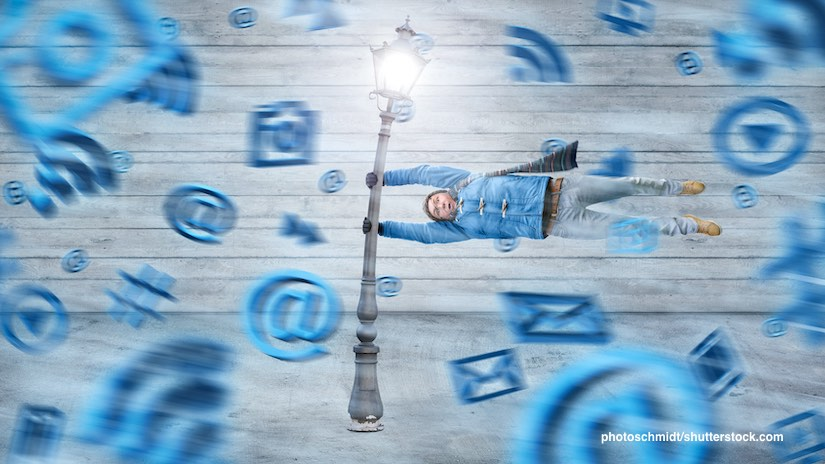 Mensch, der sich an Laterne festhält, während digitale Symbole vorbeifliegen