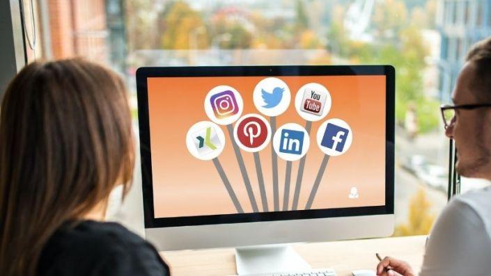 Zwei Menschen schauen sich auf einem Bildschirm Social-Media-Symbole an